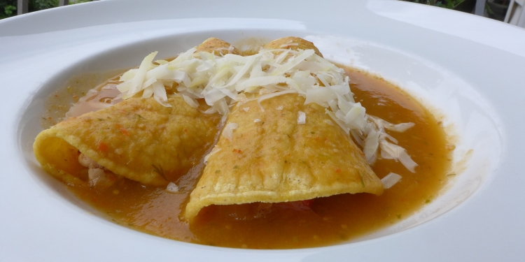 plate of Mexican enchiladas with green tomatillo sauce